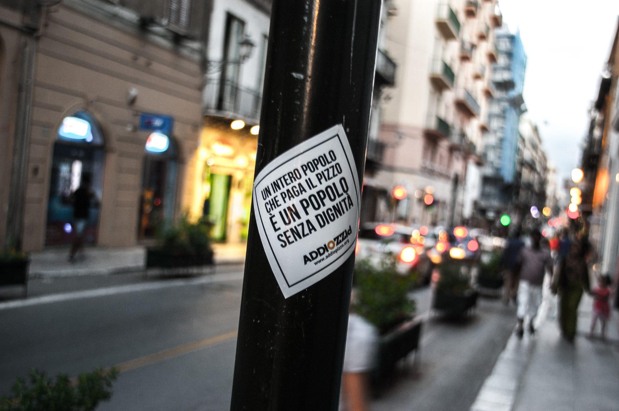 De slogan van Adio Pizzo, het antwoord van Palermo tegen de Mafia: 'Een heel volk dat zich laat afpersen is een volk zonder waardigheid'
