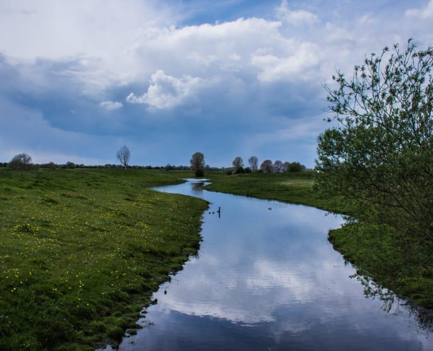 De omgeving van het Genneperhuis: de Niers, akkers en Oudhollandsche wolkenpartijen.